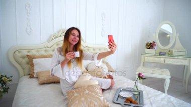 femmes sexy au lit en souriant la cam ra video 100212348. Black Bedroom Furniture Sets. Home Design Ideas