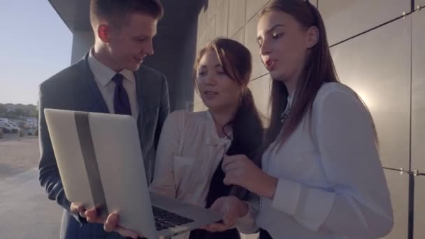 Modern Youngsters, Two Girls and Boy Study Laptop and Talking With Smiling on Background of Business Center Outdoors in Neutral Colors.