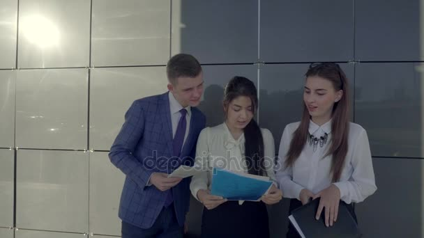 Group of Young Smart Professionals Talking, Holding in Hands Paper and See Them, on Background of Wall of Business Center Outside in Neutral Colors.