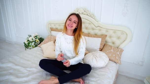 Přitažlivá dívka se těší tanec a sedí na posteli, s úsměvem v světlé ložnice.