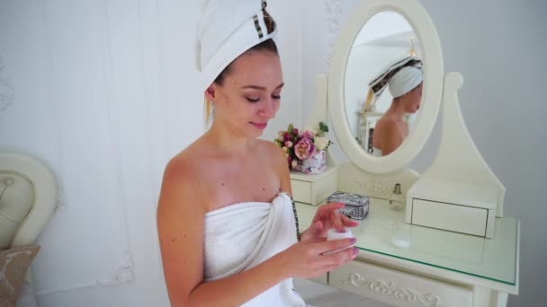 Young Female Caring For Skin Condition of Hands After Shower, Looking at Camera and Smiling, Sitting on Chair Beside Table With Mirror in Bedroom.