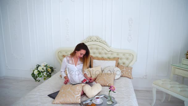 Cute Girl Leafing Through Pages of Magazine, Read Article and Sitting on Large Bed in White Bedroom Apartments and Drinking Morning Tea.