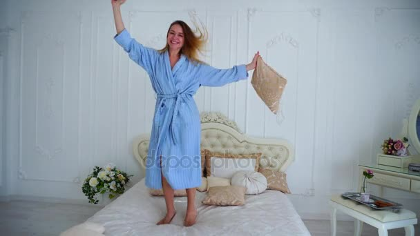 Cheerful Girl Jumping on Bed in Upright and Happy Dancing and Laughing in Bright Bedroom.
