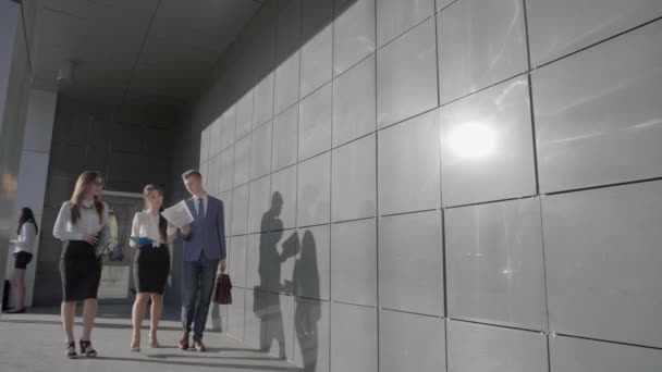 Three Self-Confident People Students go and Talk With Documentation on Background of Wall of Business Center Outside in Neutral Colors.