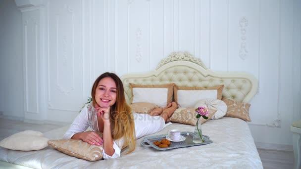 Meisje model glimlachend op camera liggend op bed in lichte