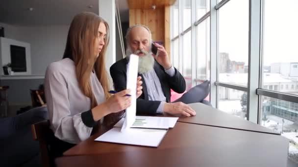 Dvě společnosti kolegy mladá dívka a starý muž mluvit o chytrého telefonu mluvit o problémech v moderní kanceláři v zimě
