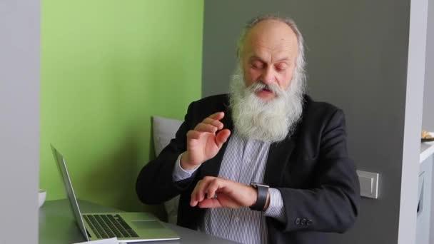 Pensionierte Alter Mann verhandelt mit Iwatch und sitzt in modernen Internet-Cafe am Tisch