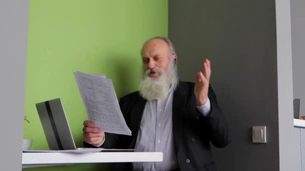 Starý muž bankéř čte schvalování dopis od šéfa a poslouchá pokyny šéfa Bluetooth Headset sedí u stolu v počítači Cafe v denní
