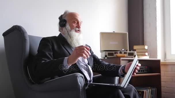 Alter Mann genießt Musik und Beats Rhythmen, sitzen mit Computer im Stuhl gegenüber Fenster tagsüber
