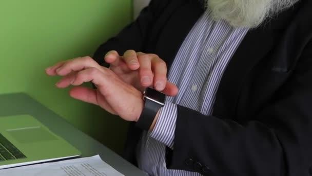 Close-up auf den Händen der älteren kluger Mann mit Gadget auf Hand beim Arbeiten mit Grafiken in modernen Internet-Cafe am Tisch.