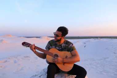 Attractive Arabian guy sings songs on guitar, sitting on hill in