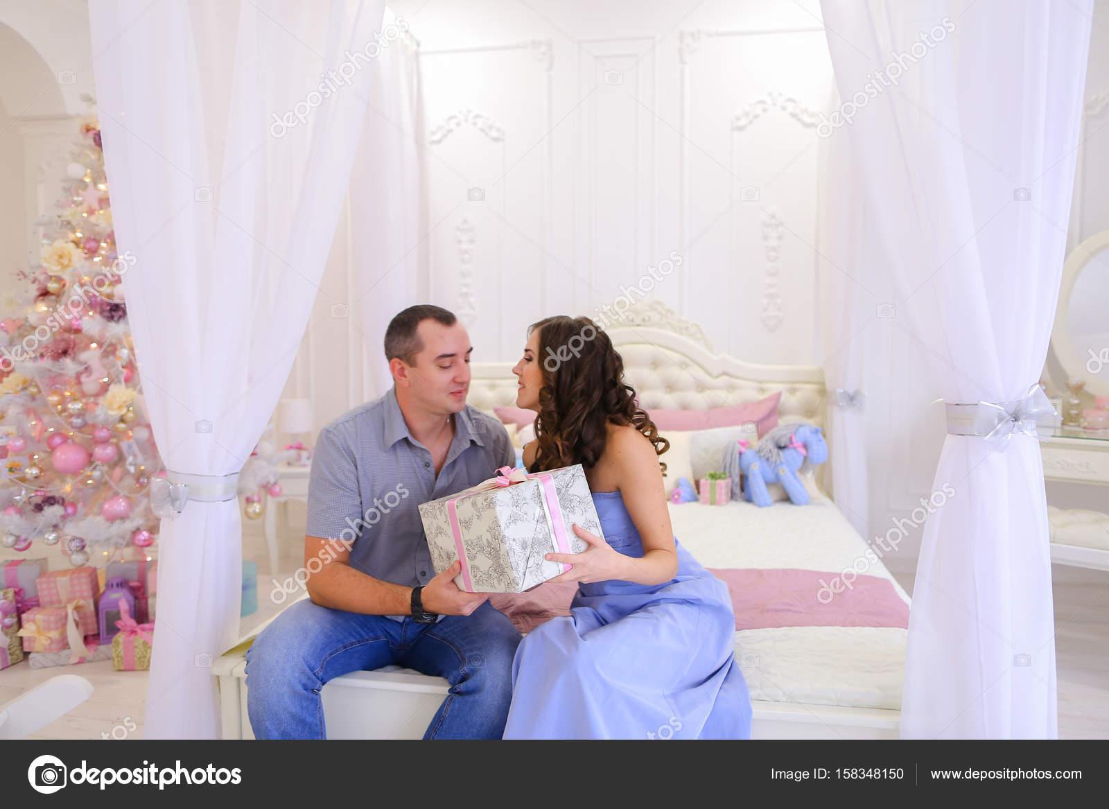 Mann und Frau geben sich gegenseitig Weihnachtsgeschenke in hellen ...