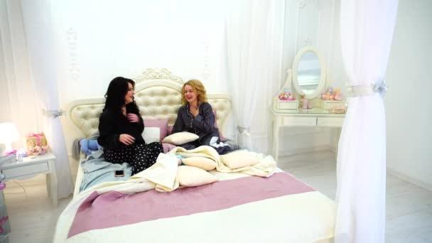 Aranyos barátnő használja a modult a szórakozás, és szocializálódnak, ült a fényes hálószoba ágy, késő este