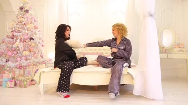 Krásné sestry v dobré náladě hrát a chovat se jako děti, sedící na posteli v ložnici světlé pozdě v noci