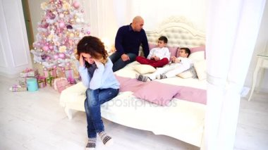 Headache and fatigue of woman, experiences before holidays. woman sits on bed on background of husband and children in bedroom with Christmas tree.