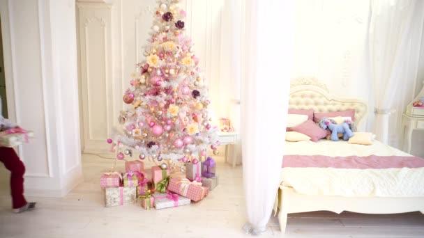 Dva chlapci připravené novoroční dárky pod vánoční stromeček z jejich synů pro rodiče ve světlé ložnici v denní
