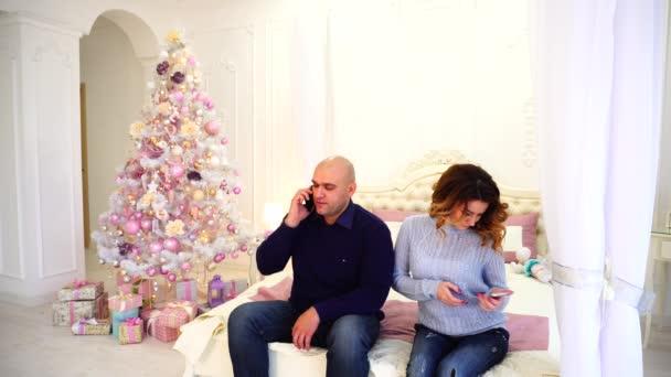 Šťastný manžel a manželka používat smartphone pogratulovat příbuzným o svátcích, sedící na posteli v ložnici s slavnostní vánoční stromeček