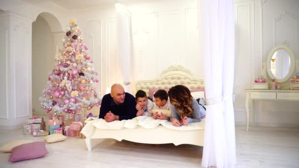 Freundliche Familie Chats mit ihren Kindern am Bett, Mama und Papa liegen lachen, auf großen Bett liegend in hellen Schlafzimmer mit Weihnachtsbaum und Geschenke