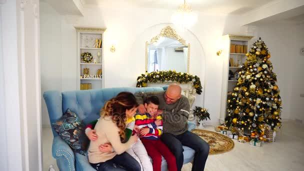 Šťastné a veselé rodiny ve slavnostní náladě mít zábavu a smích společně, sedí na modré pohovce v slavnostní zařízené místnosti s vánoční stromeček a krb v denní