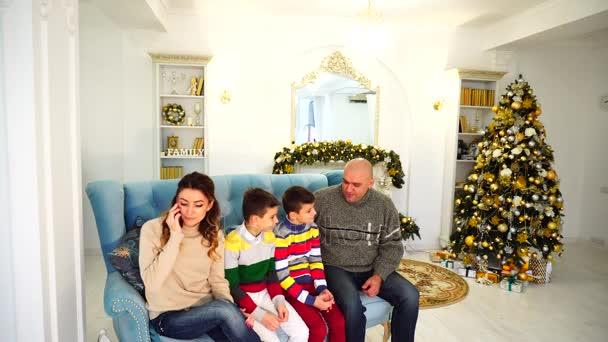 Velká rodina chatování na gauči, žena mluví o telefonu s příbuznými a ruce tube muže, který seděl na modré pohovce v slavnostní zařízené místnosti s vánoční stromeček a krb ve dne