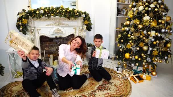 Pěkná žena a matka a děti s chlapci pohled a úsměv na kameru s dárky v jejich rukou v dobré náladě a sedět na podlaze v obývacím pokoji, zdobené svátků, s krbem a vysoká jedle