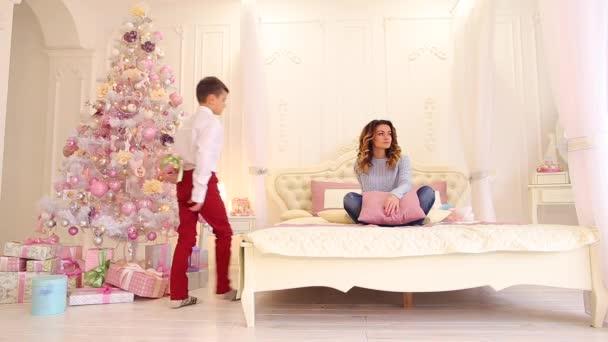 Starostlivý syn dává matka krabičky na novoroční dovolenou ve světlé ložnici s ozdobený strom a dary