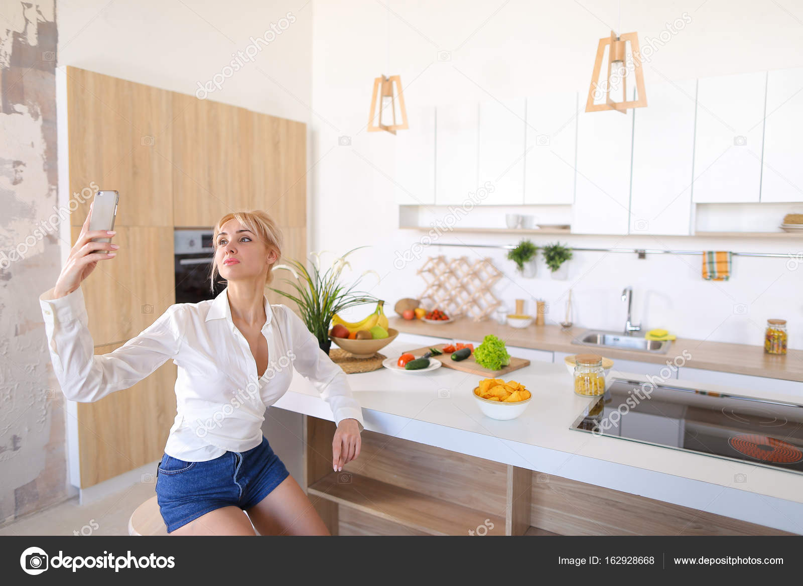 Beautiful woman doing selfie on phone on background of kitchen t ...