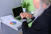 Starý muž hlavou vůdce dokončí pracovní den, sedí u notebooku na