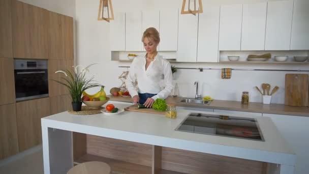 Casalinga attraente femmina taglia cetriolo con coltello e sorrisi, in  piedi al tavolo di cucina in cucina elegante
