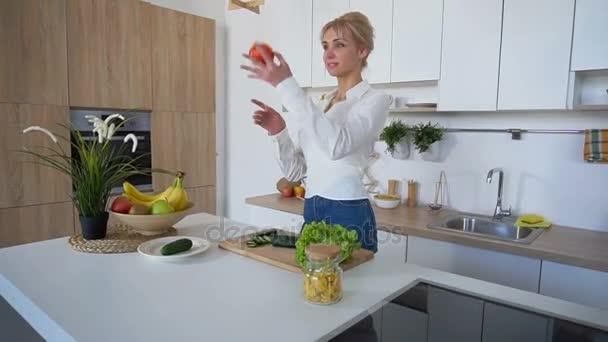 Cetriolo fette ragazza intelligente con coltello e sorrisi, in piedi al  tavolo di cucina in cucina elegante