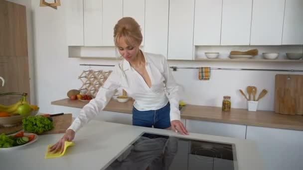Schöne Hausfrau folgt fleißig bestellen und Tücher Oberfläche, stehend in der Mitte der modernen Küche