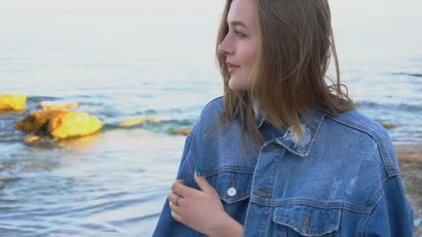 d92ab24dc4 Slow Motion Portrait of beautiful girl with light smile on lips that poses  on camera, standing against blue sea and stones on warm evening.– stock  footage