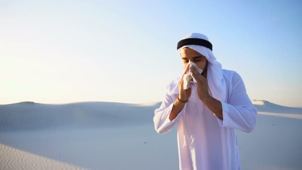 Arabian guy feels unpleasant sensations with cold, standing in middle of sandy desert on hot evening.