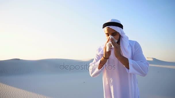 Araber fühlt sich bei Kälte unwohl, steht an einem heißen Abend mitten in der Sandwüste.
