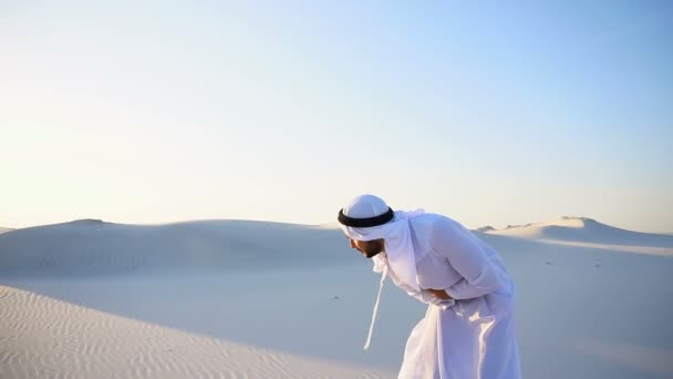 Young male emirate suffers from severe pains in abdomen, standing in middle of sandy desert on warm summer day.