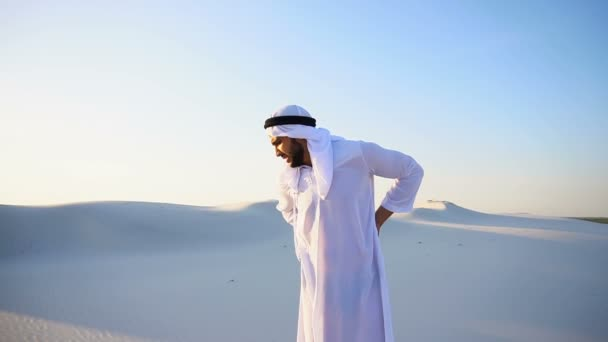 Handsome Arab sheik suffers from discomfort in back, standing in midst of sandy desert on hot summer evening.
