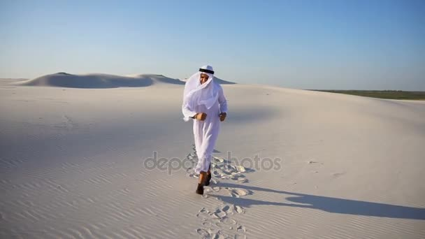 Cheerful young male Arabian UAE Sheikh emirate rejoices in life and walks through expanses of desert on clear evening.