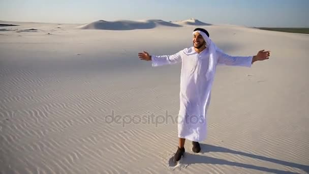 Cheerful Muslim Arabian UAE Sheikh guy walks through expanses of desert with smile on face on clear summer day.