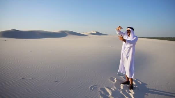 stattliche junge arabische Uae Sheikh auf der Suche nach schönen Rahmen, stehen inmitten der weiten Wüste an klaren Sommerabenden.
