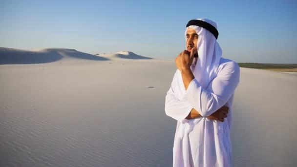stattliche arabische uae Scheich-Mann schaut hart in die Ferne und grübelt, steht mitten in der weiten Wüste an einem Sommertag.