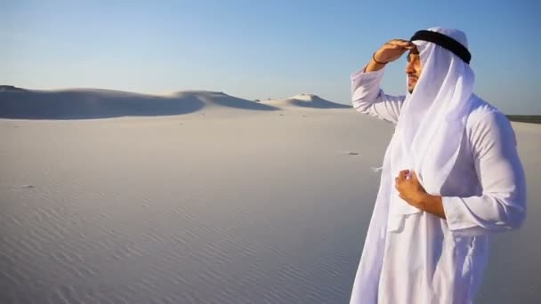 Beautiful Emirate Sheikh looks out in distance caravan of camels, standing among wide desert on hot day.