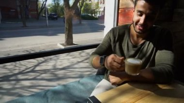 Arabian businessman waiting for partner and drinking coffee in slow motion.