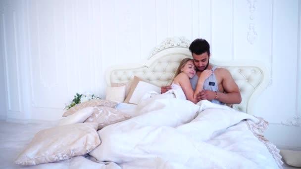Mladý manžel a manželka probudí v ráno a seznámit se s ležící pod kryty v posteli v ložnici Bright