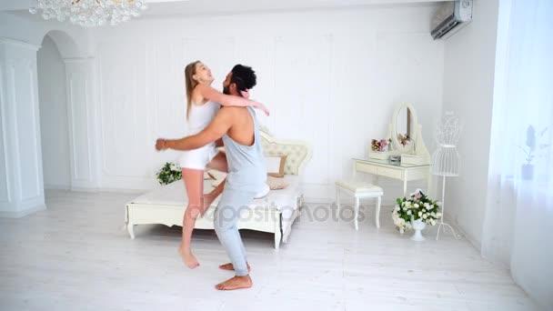 Veselý mladý manžel a manželka je vedle sebe s štěstí, objímání a směje se v ložnici na posteli pozadí a dekorace.