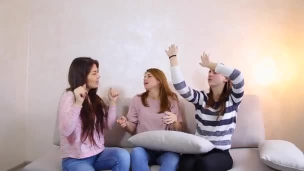 Funny girls listen to music and dance, smiles on their faces and sitting on  sofa background of light wall in room