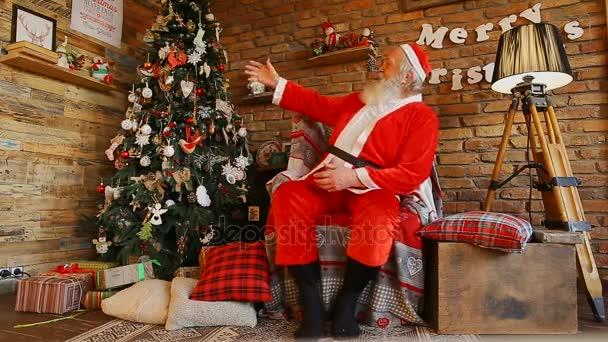 Örömteli Mikulás rögzíti a karácsonyfa