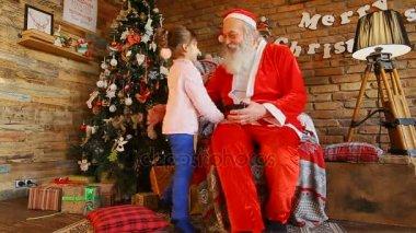 Little European girl whispers on Santas Christmas wish.