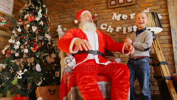 Santa tells story and plays with happy boy.