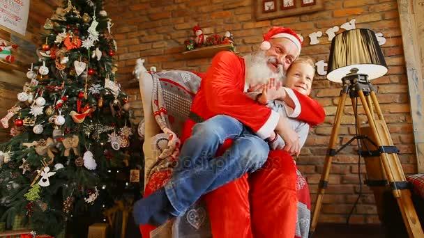 Little Boy Wellenlinien Hand und nimmt Bilder mit dem Weihnachtsmann.