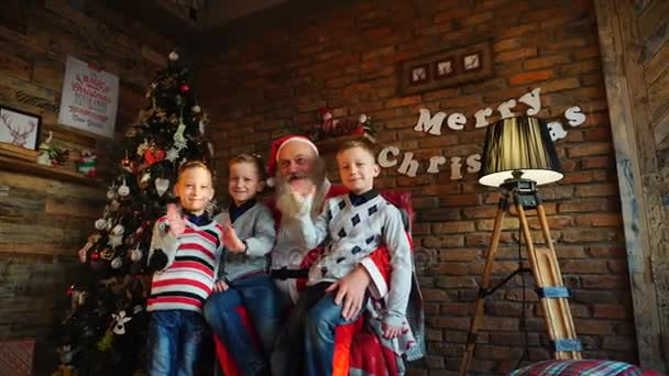 Three boys brothers make wishes to Santa Claus and send greetings with congratulations for upcoming Christmas holidays, sitting on armchair in decorated festive room